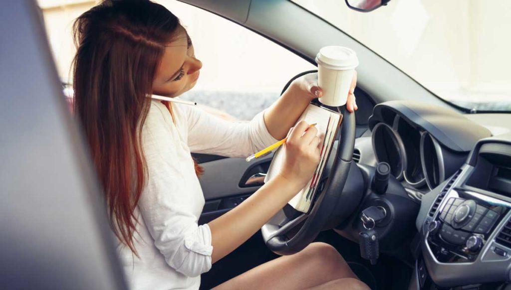 Conductora distraida tomando notas y cafe al conducir