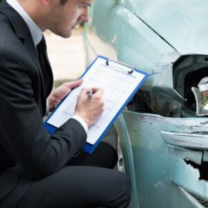 This image shows an insurance adjuster analyzing car accident damages.