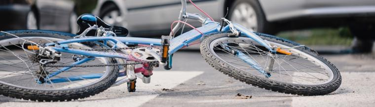 This image shows a bicycle on the ground after a collision with a car.