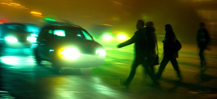 This image shows multiple people crossing a road at night as a car rapidly approaches.