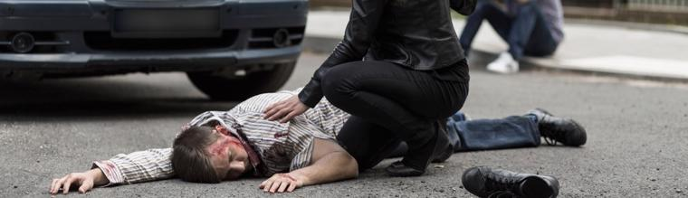 This image shows a man injured on the road after being hit by a car.