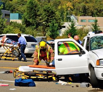 This image shows a multi-car accident with victims being taken away on stretchers.