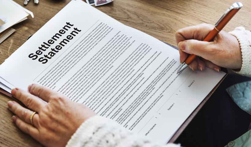 A person with a pen reading over an insurance settlement.