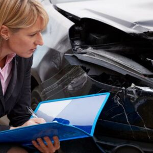 An insurance adjuster looking at a car for evidence of which driver was at fault.