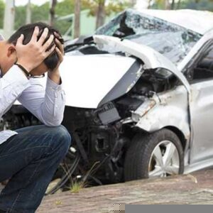 A man holding his head in his hands following a car accident.