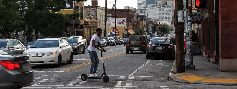 A man uses a Bird scooter in Atlanta to cross the street.
