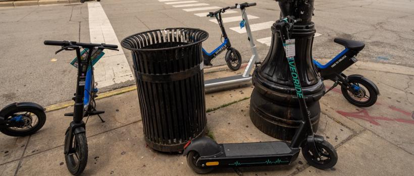 A group of rental scooters are negligently piled around a lightpost.