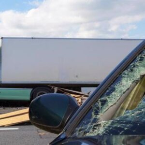 A car is seriously damaged after an accident with a truck.