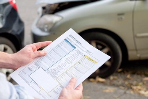 Damaged car and insurance adjuster reviewing car accident claim.